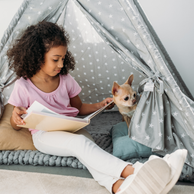 girl reading social stories with dog