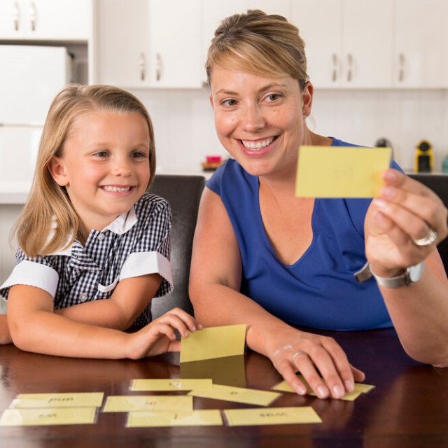 happy young mother and her sweet and beautiful little daughter playing card game at home kitchen smiling and having fun together in education and family lifestyle concept