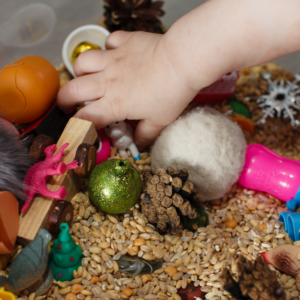 child developing motor skills through sensory box