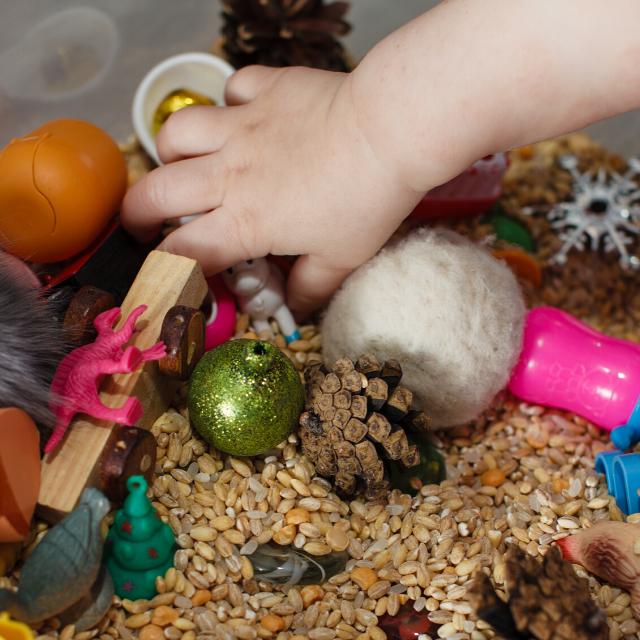 child developing motor skills through sensory box