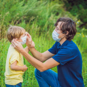 Father putting medical mask on his son