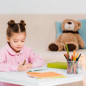 Cute little child holding pencils and studying at home