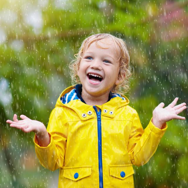 Kids playing in rain. Child on rainy day.